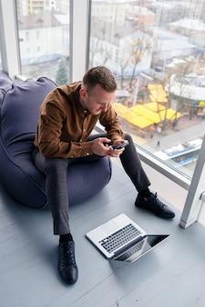 Młody, odnoszący sukcesy mężczyzna biznesmen siedzi przy dużym oknie w biurze i odpoczywa