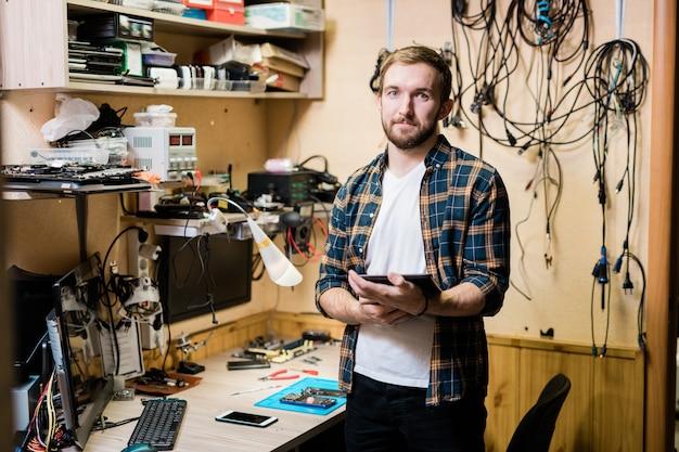 Młody, odnoszący sukcesy mistrz odzieży codziennej, trzymając jeden z zepsutych gadżetów, stojąc przy miejscu pracy przed kamerą