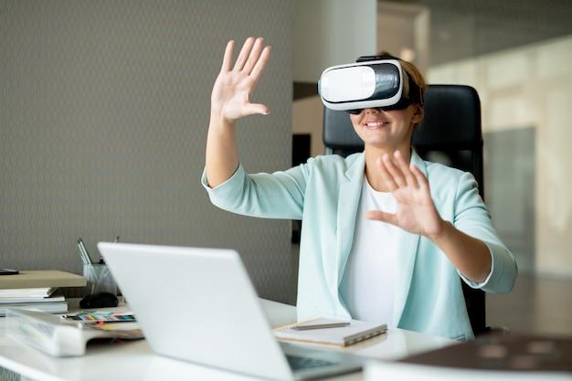Młody odnoszący sukcesy projektant oglądający wirtualną prezentację i dotykający wyświetlacza, siedząc przy biurku w biurze