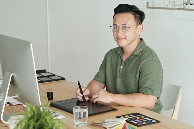 Młody, odnoszący sukcesy projektant siedzący przed monitorem