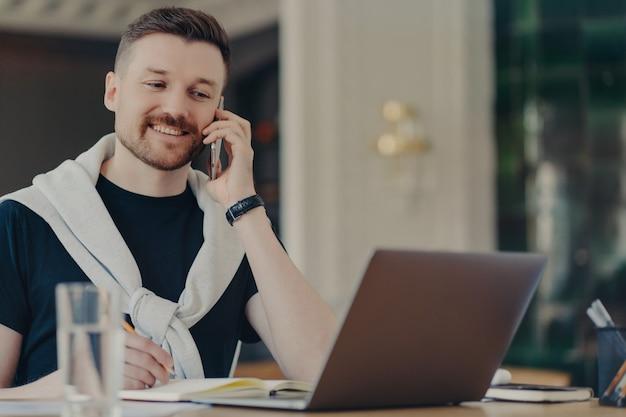 Młody odnoszący sukcesy przedsiębiorca lub męski freelancer w stroju codziennym rozmawia przez telefon komórkowy i patrząc na laptopa siedząc w miejscu pracy w biurze lub w domu, uśmiechając się i omawiając pomysły biznesowe