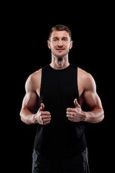 Młody odnoszący sukcesy sportowiec mięśni pokazując kciuki do góry podczas pozowania