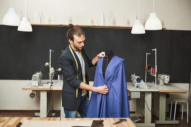 Młody ogolony przystojny kaukaski projektant mody w stylowym stroju pracuje nad nową niebieską sukienką na wiosenną kolekcję w swoim warsztacie. artysta tworzący piękne ubrania w swoim warsztacie