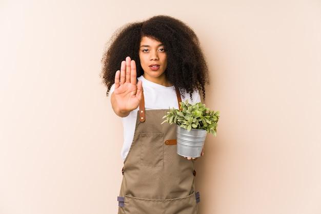 Młody ogrodnik afro trzyma plan i wyciąga rękę z wyciągniętą ręką, pokazując znak stop, uniemożliwiając ci
