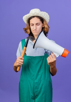 Młody ogrodnik człowiek ubrany w kombinezon i kapelusz, trzymając mini prowizji i megafon
