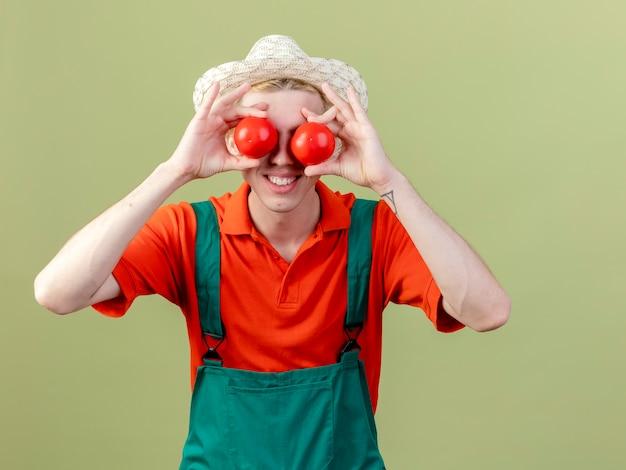 Młody ogrodnik człowiek ubrany w kombinezon i kapelusz trzymając świeże pomidory obejmujące oczy z nimi uśmiechnięty stojący na jasnym tle