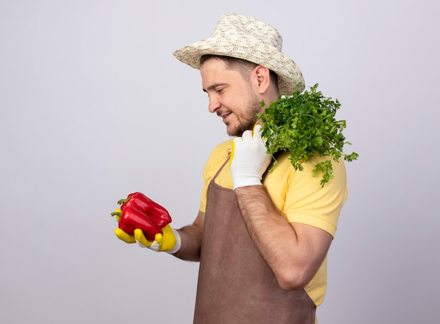 Młody ogrodnik człowiek ubrany w kombinezon i kapelusz w rękawicach roboczych, trzymając czerwoną paprykę i świeże zioła, patrząc z uśmiechem na twarzy