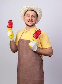 Młody ogrodnik człowiek ubrany w kombinezon i kapelusz w rękawicach roboczych, trzymając czerwoną paprykę, uśmiechając się z radosną twarzą stojącą nad białą ścianą