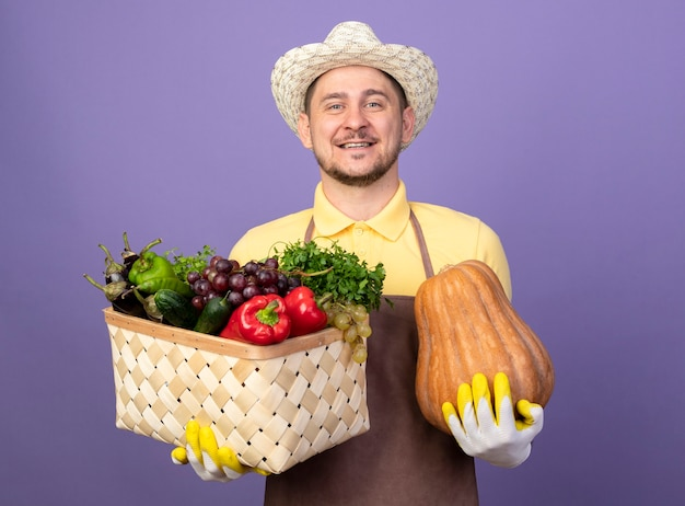 Młody ogrodnik człowiek ubrany w kombinezon i kapelusz w rękawicach roboczych, trzymając skrzynię pełną warzyw i dyni uśmiechnięty szczęśliwy i pozytywny