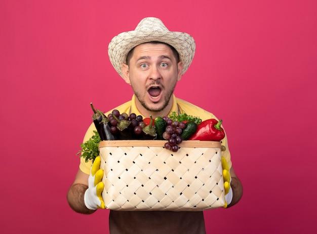 Młody ogrodnik człowiek ubrany w kombinezon i kapelusz w rękawicach roboczych, trzymając skrzynię pełną warzyw szczęśliwy i zaskoczony