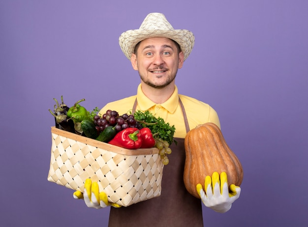 Młody ogrodnik człowiek ubrany w kombinezon i kapelusz w rękawicach roboczych, trzymając skrzynię pełną warzyw z dynią uśmiechając się z radosną buźką