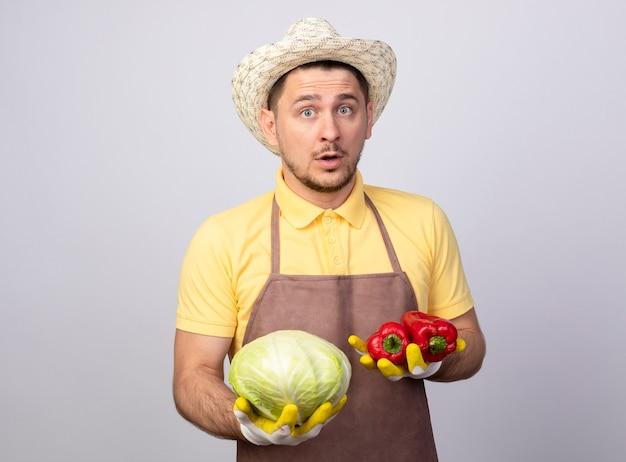 Młody ogrodnik człowiek ubrany w kombinezon i kapelusz w rękawice robocze gospodarstwa czerwona papryka i kapusta zdezorientowany