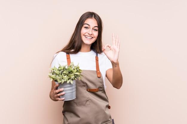 Młody ogrodnik kaukaski kobieta trzyma roślinę na białym tle wesoły i pewny siebie, pokazując ok gest.