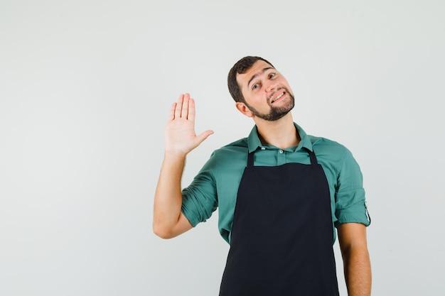 Młody ogrodnik macha ręką na pożegnanie w koszulce, fartuchu i wygląda na zadowolonego. przedni widok.