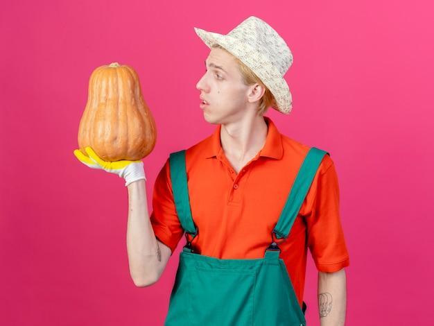 Młody ogrodnik mężczyzna na sobie kombinezon i kapelusz gospodarstwa dyni