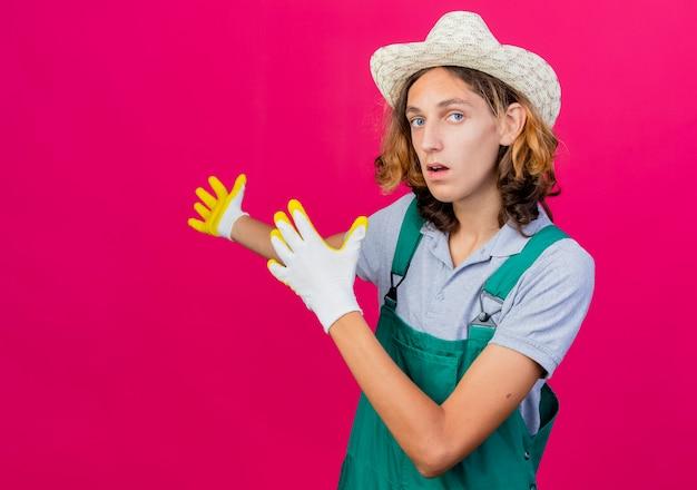 Młody ogrodnik mężczyzna na sobie kombinezon i kapelusz na sobie gumowe rękawiczki
