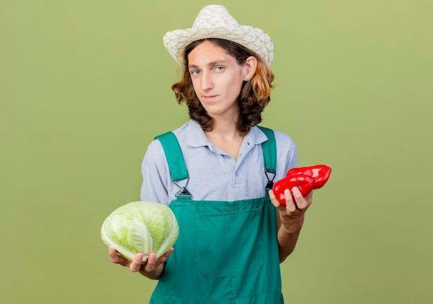 Młody ogrodnik mężczyzna na sobie kombinezon i kapelusz, trzymając kapustę i czerwoną paprykę