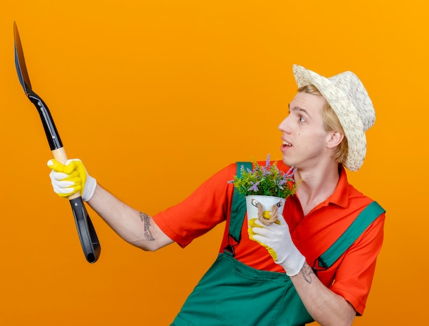 Młody ogrodnik mężczyzna na sobie kombinezon i kapelusz trzymając łopatę i roślina doniczkowa patrząc na łopatę zaskoczony stojąc na pomarańczowym tle