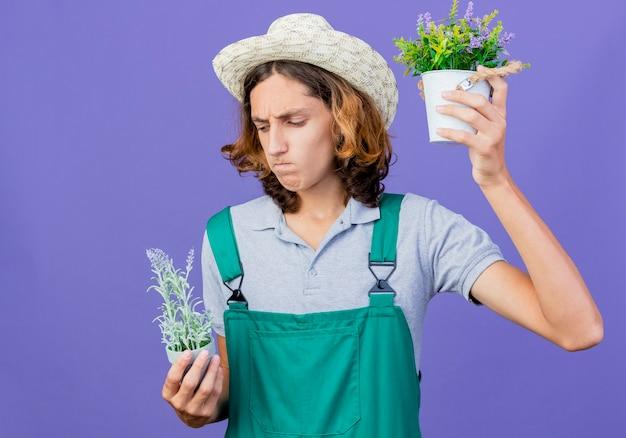 Młody ogrodnik mężczyzna na sobie kombinezon i kapelusz, trzymając rośliny doniczkowe