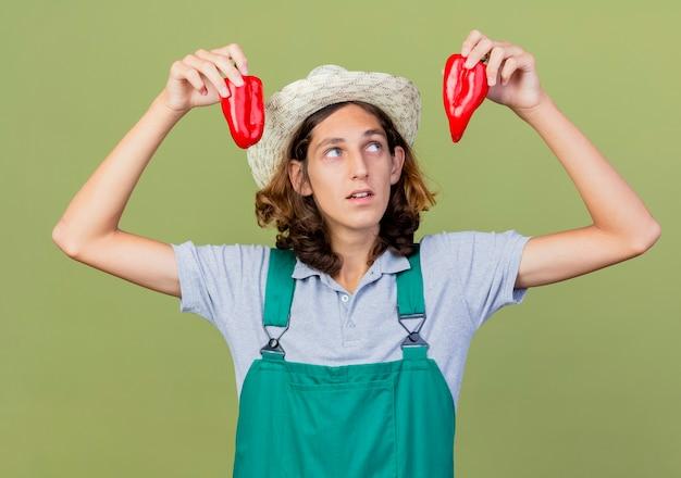 Młody ogrodnik mężczyzna ubrany w kombinezon i kapelusz gospodarstwa czerwona papryka