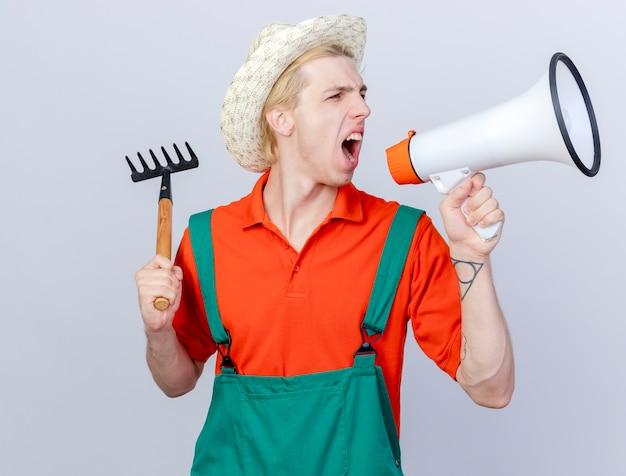 Młody ogrodnik mężczyzna ubrany w kombinezon i kapelusz kołyszący mini grabie krzyczący do megafonu z gniewnym wyrazem stojącym na białym tle