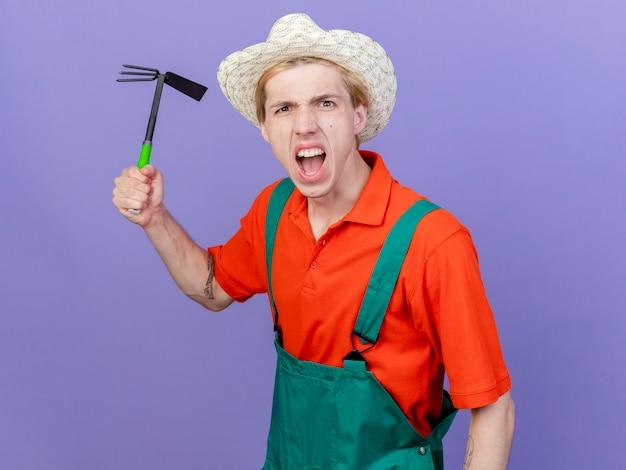 Młody ogrodnik mężczyzna ubrany w kombinezon i kapelusz kołyszący się macka z gniewną twarzą
