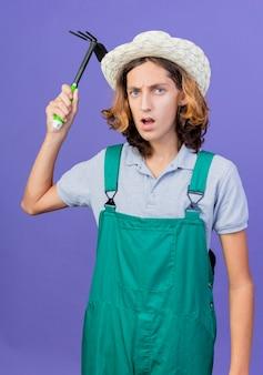 Młody ogrodnik mężczyzna ubrany w kombinezon i kapelusz kołyszący się macka