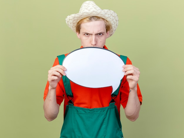 Młody ogrodnik mężczyzna ubrany w kombinezon i kapelusz pokazujący pusty znak bańki mowy looki na aparat z marszczącą brwią poważną twarz stojącą na jasnym tle