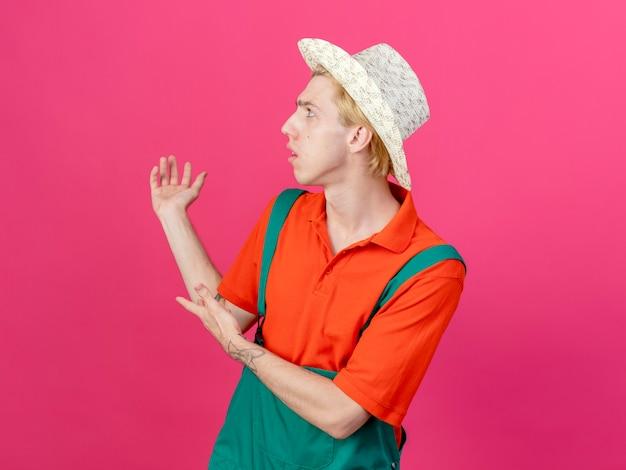 Młody ogrodnik mężczyzna ubrany w kombinezon i kapelusz przedstawia coś