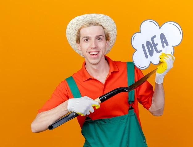 Młody ogrodnik mężczyzna ubrany w kombinezon i kapelusz, trzymając łopatę i znak bańki mowy