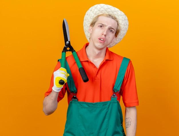 Młody ogrodnik mężczyzna ubrany w kombinezon i kapelusz trzymając nożyce do żywopłotu na ramieniu