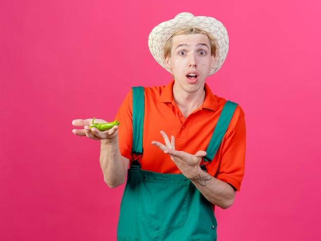 Młody ogrodnik mężczyzna ubrany w kombinezon i kapelusz trzymając połówki zielonej papryki chili