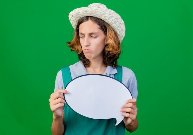 Młody ogrodnik mężczyzna ubrany w kombinezon i kapelusz trzymając pusty znak bańki mowy