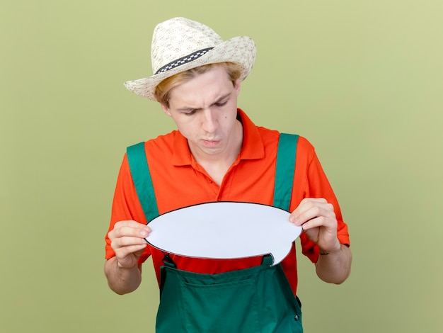 Młody ogrodnik mężczyzna ubrany w kombinezon i kapelusz trzymając pusty znak bańki patrząc na niego z zainteresowaniem stojąc na jasnym tle