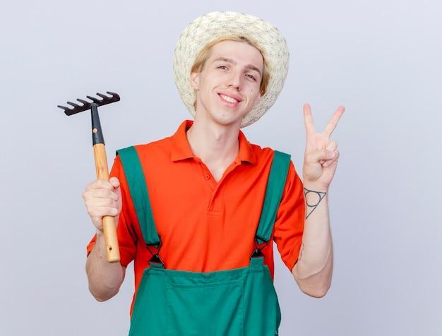 Młody ogrodnik mężczyzna ubrany w kombinezon i kapelusz trzymający mini grabie patrząc na kamery uśmiechnięty radośnie i pozytywnie pokazujący numer dwa stojący na białym tle
