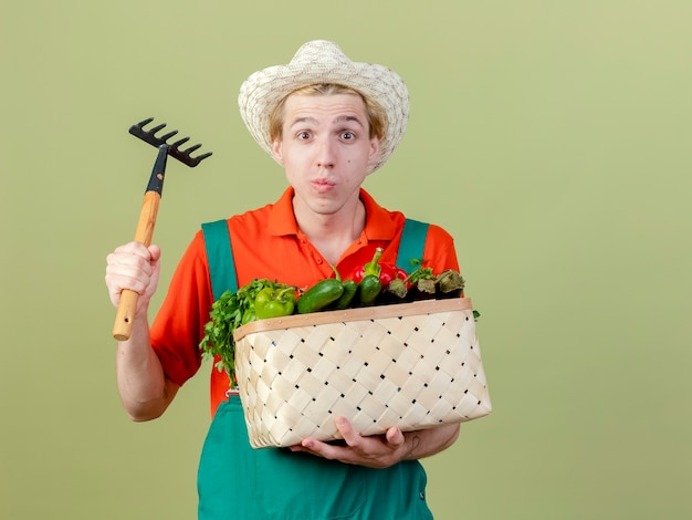 Młody ogrodnik mężczyzna ubrany w kombinezon i kapelusz trzymający skrzynię pełną warzyw i mini grabie patrząc na aparat zdezorientowany stojąc na jasnym tle