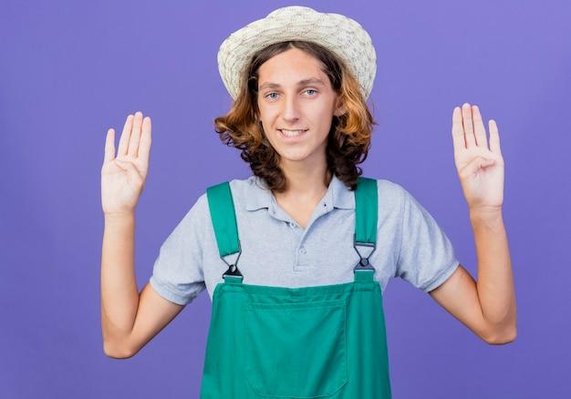 Młody ogrodnik mężczyzna ubrany w kombinezon i kapelusz uśmiechnięty wyświetlono numer osiem