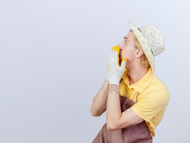 Młody ogrodnik mężczyzna ubrany w kombinezon i kapelusz w gumowych rękawiczkach zakrywających usta rękami potrząsanymi, patrząc na coś