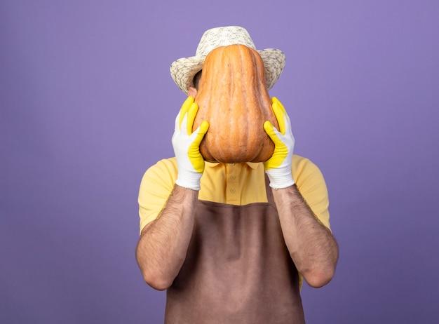 Młody ogrodnik mężczyzna ubrany w kombinezon i kapelusz w rękawicach roboczych trzymając dyni, ukrywając twarz za nim