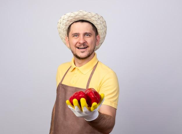 Młody ogrodnik mężczyzna ubrany w kombinezon i kapelusz w rękawice robocze pokazujące czerwoną paprykę uśmiechnięty z radosną buźkę