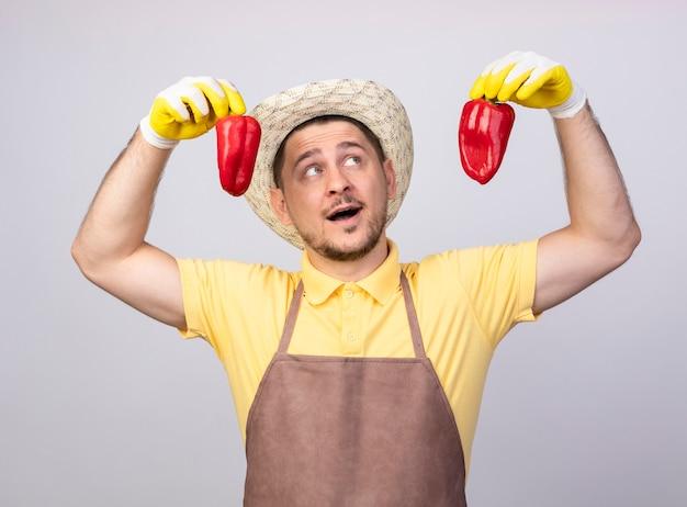 Młody ogrodnik mężczyzna ubrany w kombinezon i kapelusz w rękawice robocze, trzymając czerwoną paprykę, uśmiechając się radośnie
