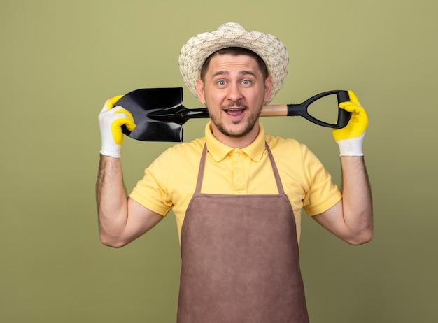Młody ogrodnik mężczyzna ubrany w kombinezon i kapelusz w rękawice robocze trzymając łopatę uśmiechnięty z radosną buźkę