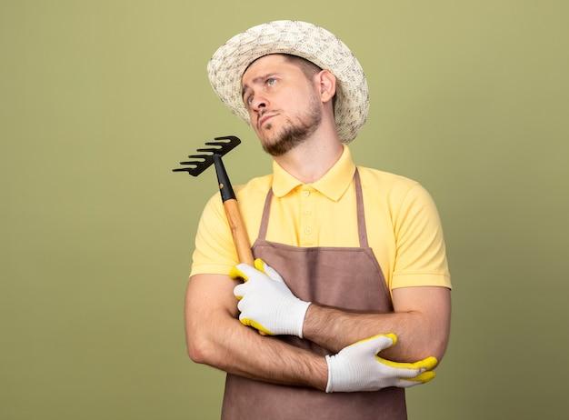 Młody ogrodnik mężczyzna ubrany w kombinezon i kapelusz w rękawiczkach roboczych, trzymając mini grabie, patrząc na bok zdziwiony stojąc nad jasną ścianą