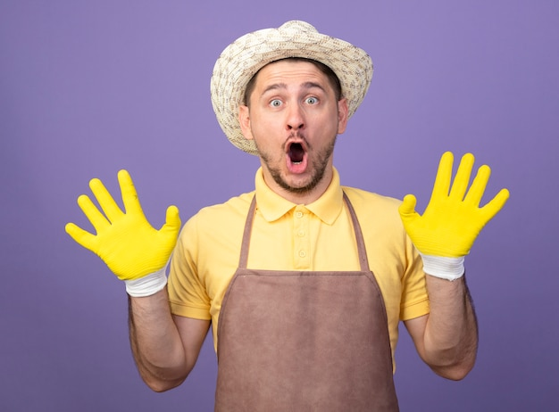 Młody ogrodnik mężczyzna ubrany w kombinezon i kapelusz w roboczych rękawiczkach patrząc z przodu zdumiony i zaskoczony podnosząc ręce w kapitulacji stojąc nad fioletową ścianą