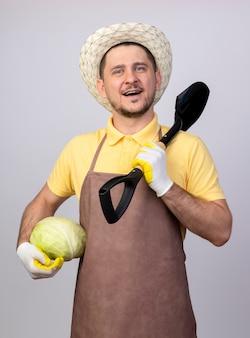 Młody ogrodnik mężczyzna ubrany w kombinezon i kapelusz w roboczych rękawiczkach trzymający kapustę i łopatę patrząc z przodu z uśmiechem na twarzy stojącej nad białą ścianą