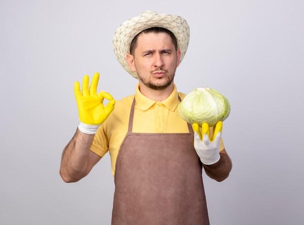 Młody ogrodnik mężczyzna ubrany w kombinezon i kapelusz w roboczych rękawiczkach trzymający kapustę patrząc z przodu z pewnym siebie wyrazem twarzy, pokazując znak ok stojąc nad białą ścianą
