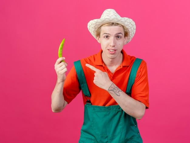 Młody ogrodnik mężczyzna ubrany w kombinezon i kapelusz wskazujący zieloną papryką chili