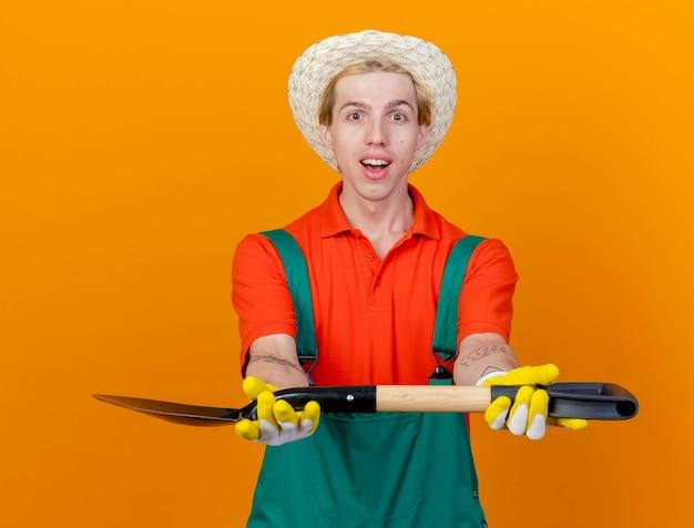 Młody ogrodnik mężczyzna ubrany w kombinezon i kapelusz wykazujące łopatę patrząc na kamery uśmiechnięty szczęśliwy twarz stojącej na pomarańczowym tle