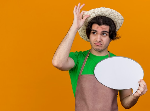 Młody ogrodnik mężczyzna w fartuchu i kapeluszu trzymający pusty znak bańki mowy patrząc na bok, zdezorientowany i niezadowolony, dotykając swojego kapelusza stojącego nad pomarańczową ścianą