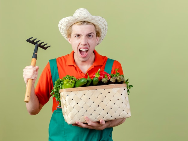 Młody ogrodnik mężczyzna w kombinezonie i kapeluszu, trzymając skrzynię pełną warzyw i mini grabie patrząc na kamerę, krzycząc z agresywnym wyrazem twarzy, stojąc na jasnym tle